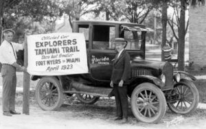 Explorers Tamiami Trail sign in front of an old automobile