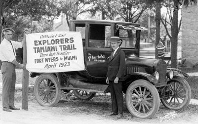 Explorers posing in front of an old car with a Tamiami Trail sign